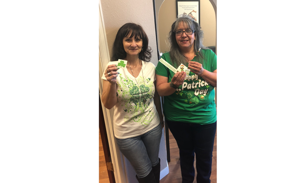 Agent Julie Yalotz with female staff member, wearing St Patrick's Day attire.