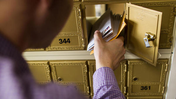 Close up of hand taking mail from mailbox