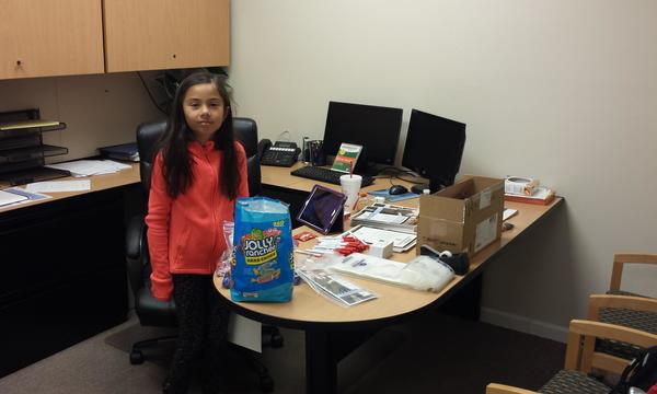Randall's daughter standing by his desk next to a very large bag of candy