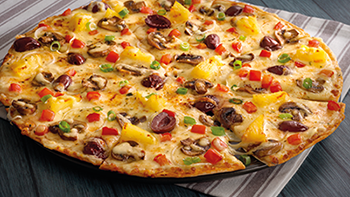 Pizza with mushrooms, pineapple, peppers and cheddar cheese on a plate.