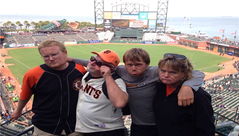 Family posing with sad faces at a baseball game
