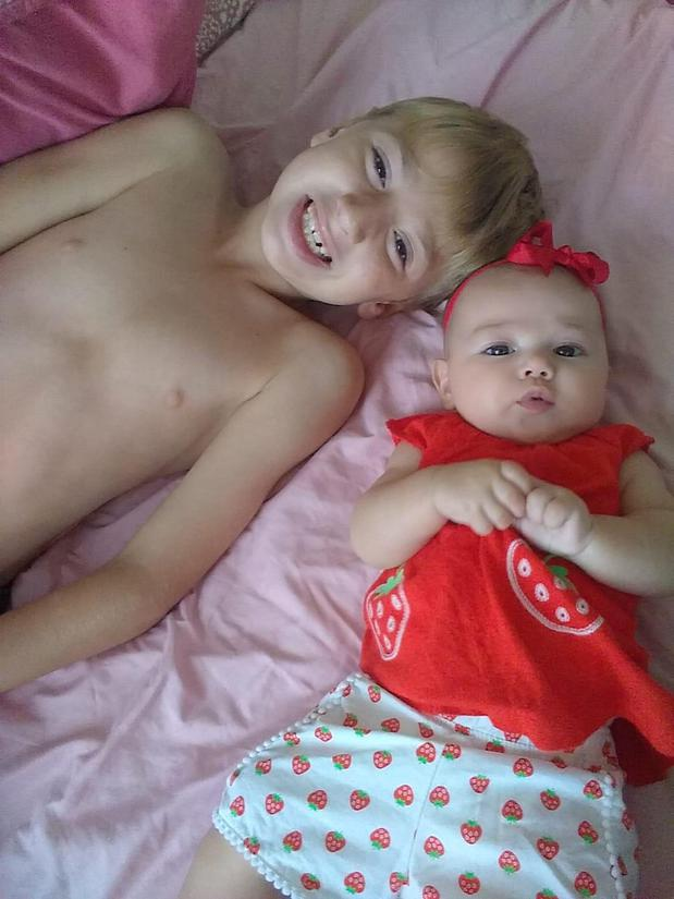 Boy and a baby girl laying on the bed