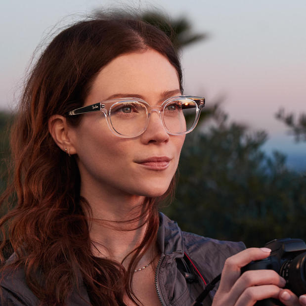 Woman holding camera while wearing LensCrafters eyeglasses
