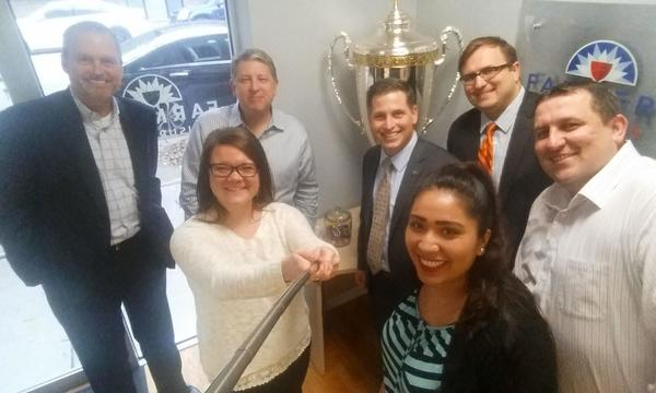 Seven people using a selfie stick to pose in front of a trophy.