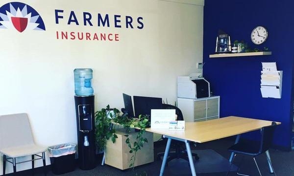 Desk in the corner of an office next to a wall displaying the Farmers logo