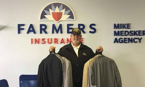 An older man holding many suits in his hand with Farmers® logo in the background.