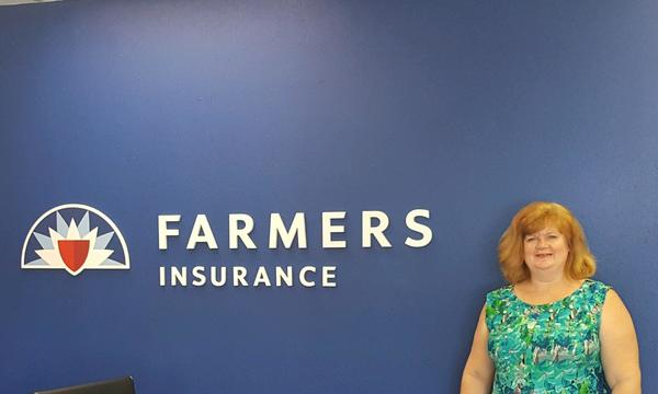 Woman in front of Farmers logo on wall