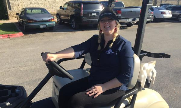 Staff member Veronica in a golf cart.