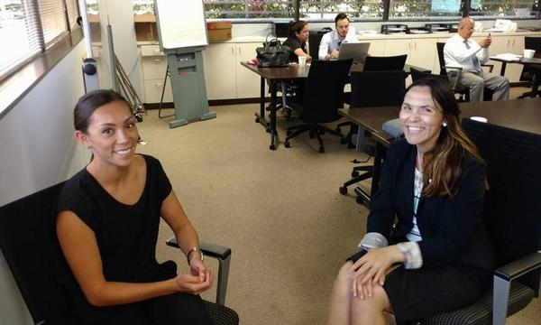 2 female colleagues sitting in chairs facing each other in an office.