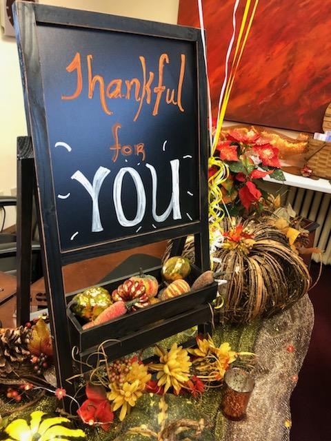 "A beautiful Fall themed chalkboard sign that reads ""Thankful for You"" and is surrounded by many leaves and pumpkin decorations."