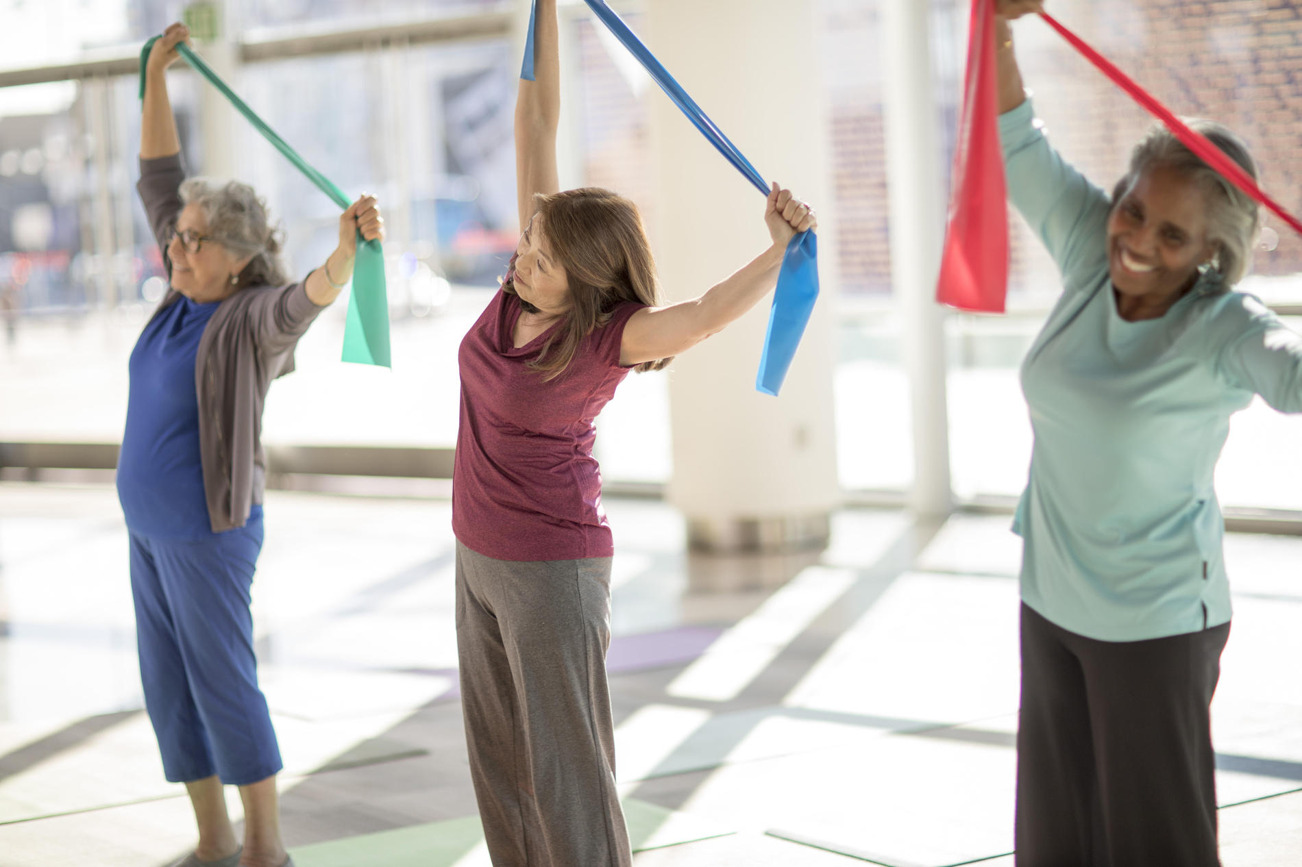 Three senior women stretching in exercise class