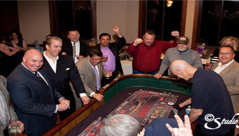 People standing around a casino table