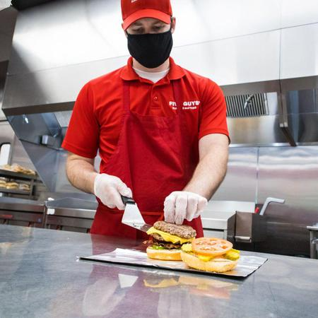 A Five Guys crew member constructs a cheeseburger