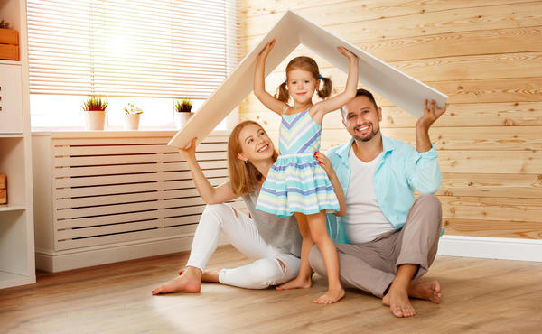 family of three posing with a roof over their heads symbolizing home insurance coverage