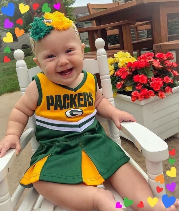 Baby in a packers outfit in a chair