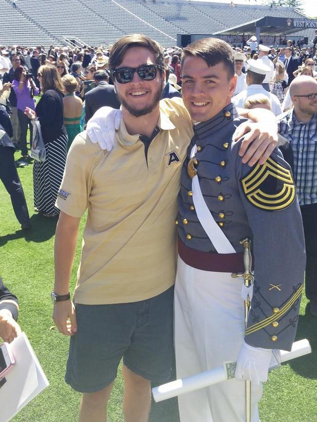 A man posing with his graduating brother in uniform.