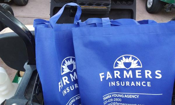 Two blue Farmers Insurance branded tote bags