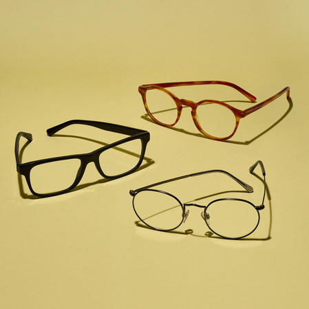 Collection of three prescription eyeglasses on a solid yellow background