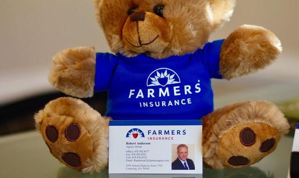 A small teddy bear wearing a Farmers Insurance sweater sits on a desk