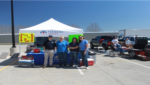 A group of adults standing in front of a Farmers tent.