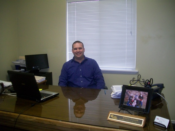 A photo of Farmers agent Kyle Fuller sitting at his desk with a laptop and picture frames.