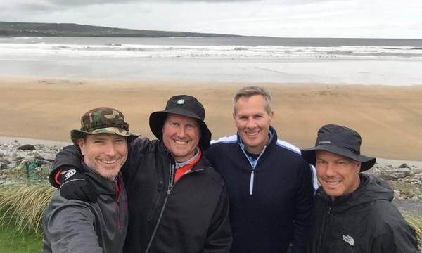 Agent Jeff Hazen with three male friends standing on a beach in Ireland.