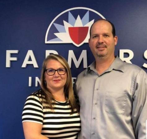 Couple posing in front of Farmers Insurance wall