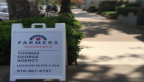 Street sign with the agents name and the Farmers Insurance logo
