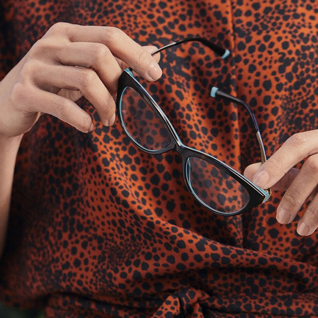 Woman in cheetah print shirt holding prescription eyeglasses