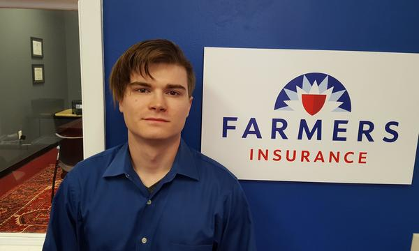 Michael Benham Agency staff member, Daniel Oliver, in a blue collared shirt next to the Farmers logo on a blue wall.