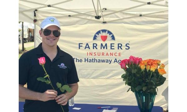 Farmers Insurance staff posing with roses in a Farmers tent