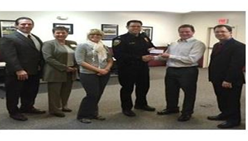 Farmers Agent presenting a donation to a police officer.