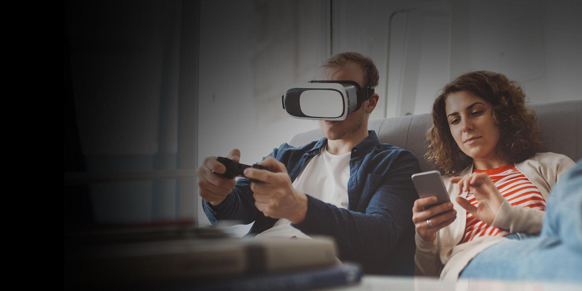 Photo of two people on a couch using Suddenlink high-speed internet connected devices - one playing video games on a virtual reality headset while another scrolls on a smartphone