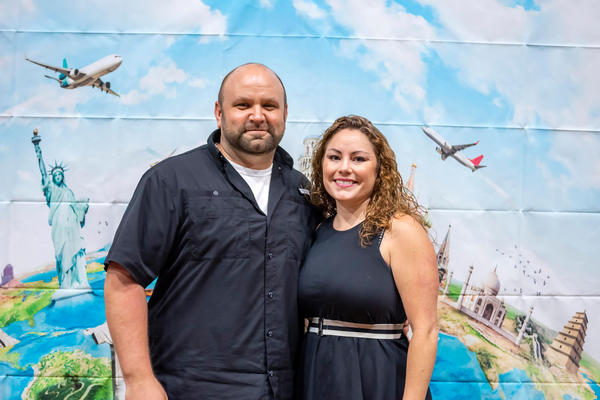Two people posing in front of a mural