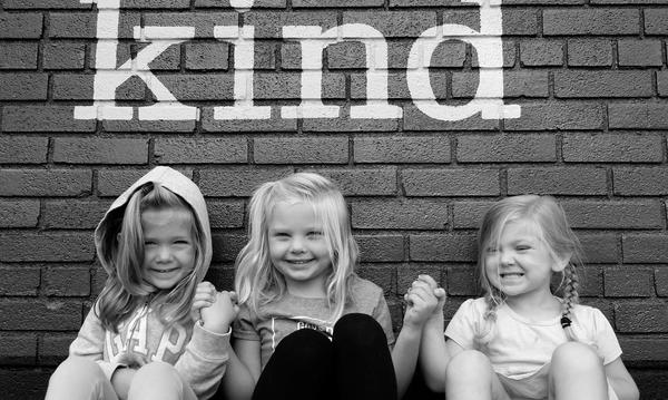 "3 little girls sit against a wall with ""kind"" written on it"