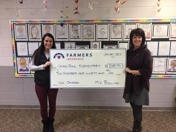 Agent Marta-Karin Bolling presenting a check to a local school teacher.