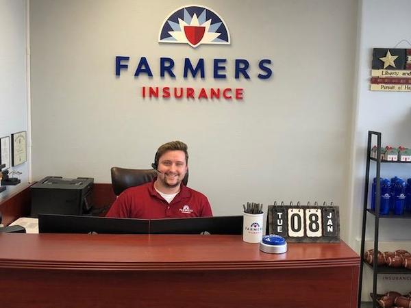 agent sitting in front of farmers sign