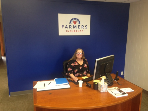Woman sitting at a desk underneath a Farmers sign