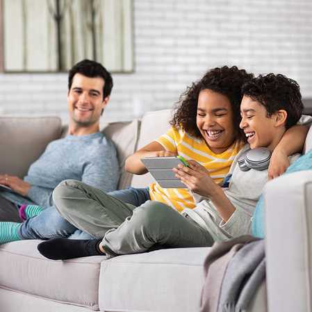 A father sits on a couch using his laptop as his children watch a movie on their tablet using COX Communications to stay connected.