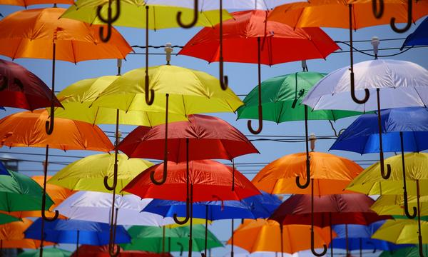 Wide variety of colorful umbrellas against a blue sky.