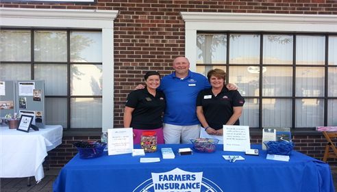 Agent standing with a man and woman in front of a Farmers table
