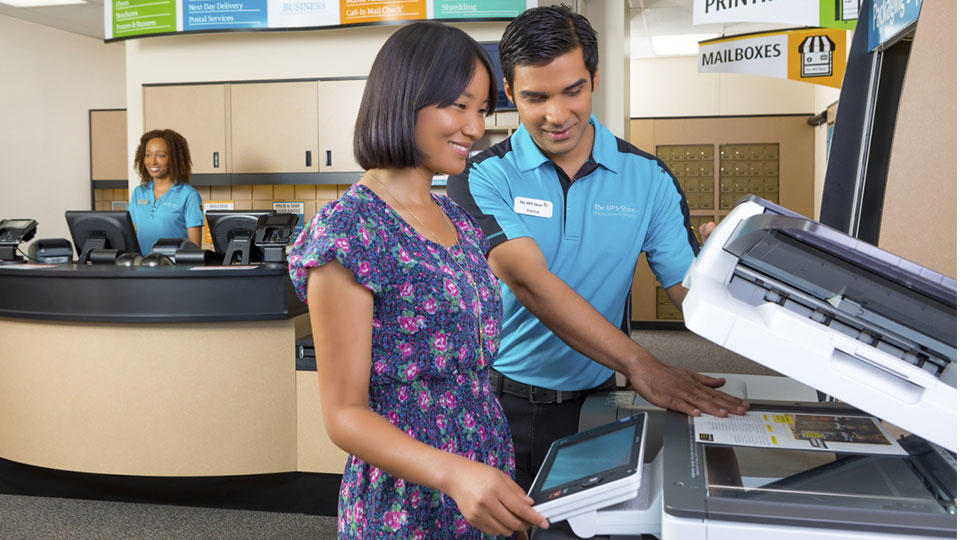 Employee assists customer at copier