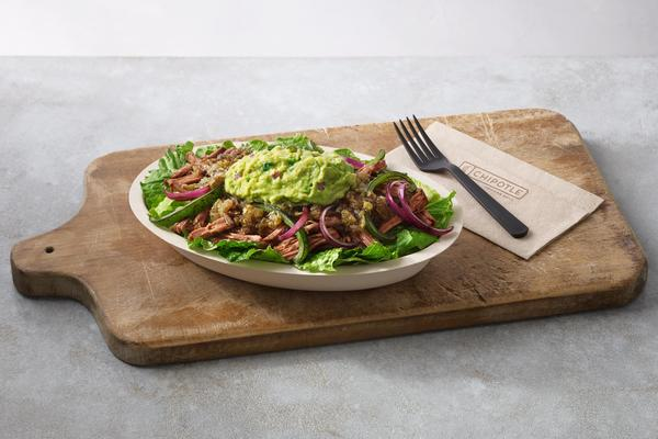 Paleo salad bowl on a wooden cutting board with a fork and napkin