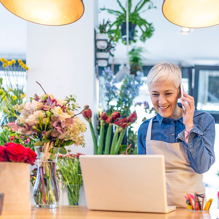 Florist using phone and computer for online banking