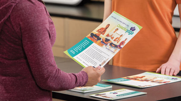 Customer holding a Yoga flyer at the counter
