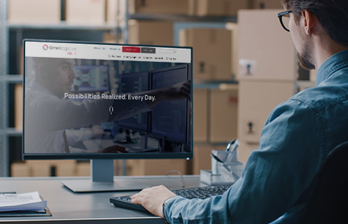Man looking at Omni Logistics technolgy solutions on website on computer screen