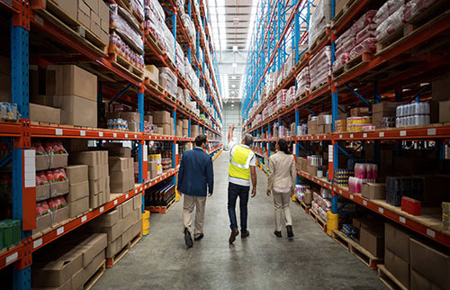 Inside Omni Logistics warehouse with worker walking with customers in between racks showing warehousing and distribution logistics solutions