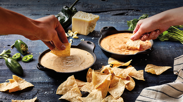 On the left hand dipping a chip into Qdoba's 3-Cheese Queso & another hand on the right dipping a chip into Quoba's Queso Diablo with a stack of chips lining the foreground.