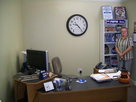 A photo of staff member Marcene standing in front of a bookcase and behind her office desk.