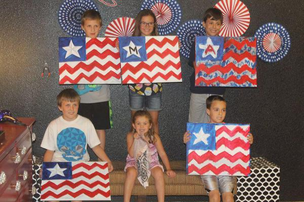 children holding paper American flags